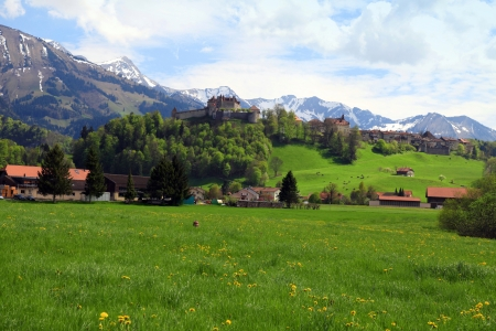 gruyere: Beautiful landscape with Gruyere Castle, fields and Alps Mountains in the background, Switzerland Stock Photo