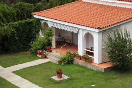 Beautiful white house with red tile roof, small terrace and lawn in the garden.