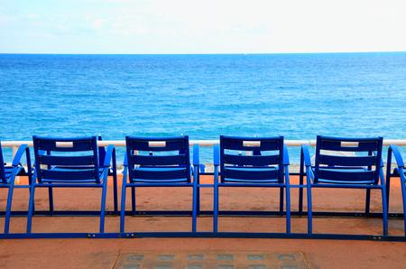 プロムナード ・ デ ・ ザングレ、ニース、フランスの青色の空の椅子