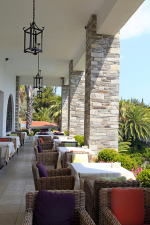 Mediterranean cafe terrace with wicker chairs and multicolored cushions overlooking the tropical garden, Greece