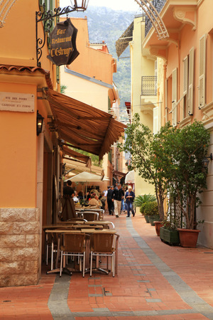 carlo: MONACO, MONTE-CARLO - MAY 15: Narrow street with old houses and sidewalk cafe at May 15,2013 in Monaco, Monte Carlo.