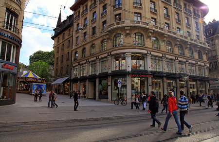 rue: Geneva, Switzerland - May 10, 2013: People walking on Rue du Marche, main shopping street in the center of Geneva. Rue du Marché is a shopping street with fashion stores, electronics, bookshops and several department stores with clothes, furnishings and