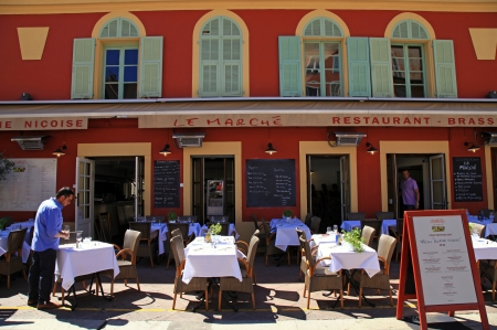 Nice, France – May 13, 2013: Outdoor french restaurants with typical Nicoise cuisine on the Cours Saleya - is the most active and traditional square in Nice, with its daily flower market. Cours Saleya is one of the most famous market areas and main attr