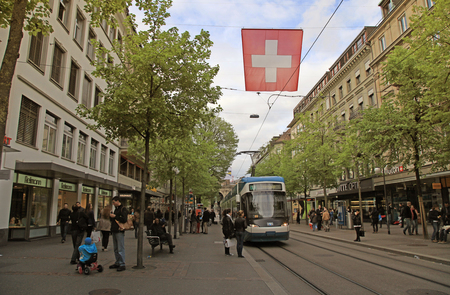 sidewalks: Zurich, Switzerland - May 04, 2013: A tram drives down the center of Bahnhofstrasse while people walk on the sidewalks in Zurich, Switzerland. A Swiss flag hangs above the street.  Bahnhofstrasse is one of the most expensive shopping streets in the world,