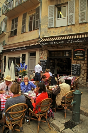 Nice,  France - May 14, 2013: People having lunch at beautiful french outdoor cafe in the old town Nice - the largest resort and tourist town on the French Riviera, Cote dAzur, France.