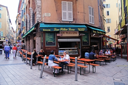 Nice,  France - May 14, 2013: People having lunch at french outdoor cafe in the Old town Nice - the largest resort and tourist town on the French Riviera, Cote d'Azur, France.