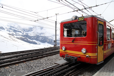 loc: May 07,2013: Railway station with red swiss train in Jungfrau, Switzerland. Train starts from Kleine Scheidegg and takes you directly to the Jungfraujoch-Top of Europe.