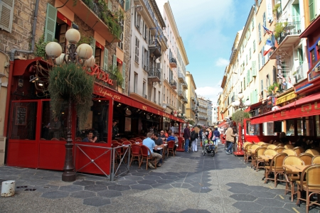Nice, France - May 14, 2013 : Narrow pedestrian street in Old Town of Nice, France with sidewalk cafes, souvenir shops and tourists walking around at May 14, 2013.