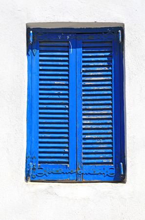 Vintage blue close window with shutters in old white stone wall photo