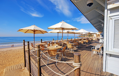 Summer outdoor terrace cafe on sand beach of Atlantic ocean (Algarve,Portugal)