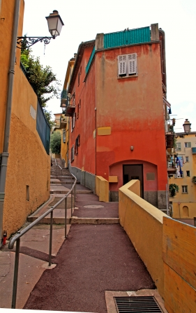 Multicolored houses and steps on narrow street in the old town of Nice, French Riviera (Cote d'Azure), France.  photo