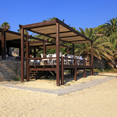 Summer outdoor terrace cafe on sand beach (Greece), square shape image