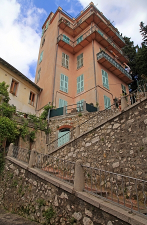 Old houses with green shutters and stone steps on narrow street in Nice, French Riviera (Cote d'Azure), France.