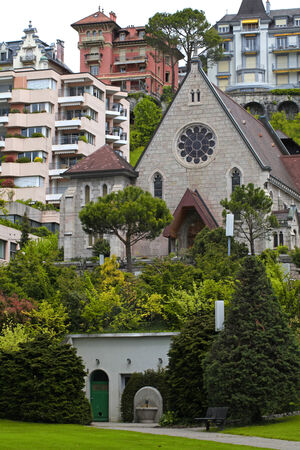 Beautiful vertical view with trees, buildings and small chapel in Montreux, Switzerland