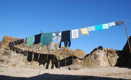 Laundry hanging out to dry outdoors in a poor stone village, Portugal photo