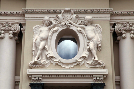 angel statues and oval window at baroque style facade, Monaco photo
