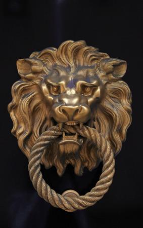 茶色の木製の背景に真鍮のライオンの形でアンティーク ドアノブ 写真素材