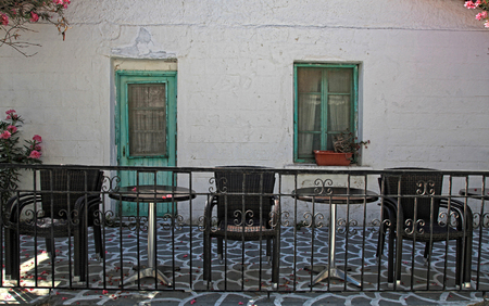 old house with sidewalk patio and outdoor furniture, Greek islands photo