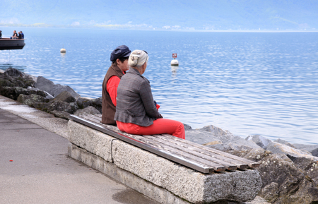 MONTREUX, SWITZERLAND - MAY 9: Two senior women relaxing on the banch at lake Geneva waterfront in Montreux, Switzerland on May 9, 2013.