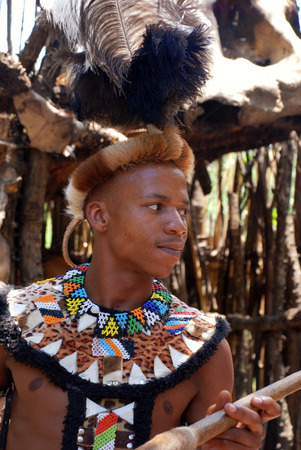 LESEDI VILLAGE, SOUTH AFRICA - JANUARY 1,2008: Zulu man wearing warrior tribal dress on January 01, 2008 in Lesedi Cultural village, South Africa. Men in Zulu clan wear animal skin decorated multicolored beads to cover themselves.