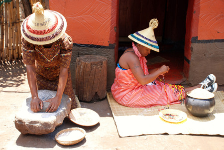 LESEDI,SOUTH AFRICA - JAN 1, 2008:Sotho women in handmade dress and conical hat cooking maize meal and weave beaded jewelry at tribal house on January 1,2008 at Lesedi Cultural Village,South Africa.