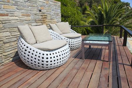 Blanco muebles de exterior sillones de mimbre y mesa redonda de cristal en la terraza de madera
