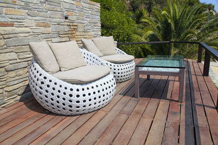 White outdoor furniture round rattan armchairs and glass table on wood terrace Stock Photo