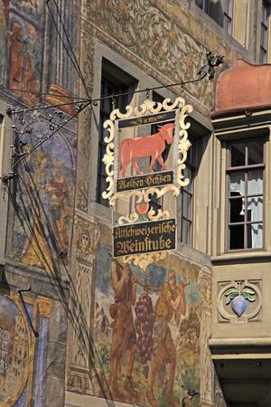 STEIN AM RHEIN, SWITZERLAND - MAY 05, 2013: Old beautiful fresco and signboard of restaurant on medieval building in Stein am Rhein, Switzerland