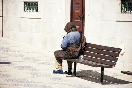 LISBON, PORTUGAL - MAY 01, 2009: A unrecognizable homeless man on a bench in Lisbon, Portugal.