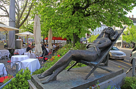 ZURICH, SWITZERLAND - MAY 05, 2013: Outdoor cafe and restaurants in the shade of trees and park statue of relax woman in deck chair, the center of Zurich, Switzerland