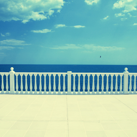 Summer view with classic white balustrade and empty terrace overlooking the sea (Italy) photo