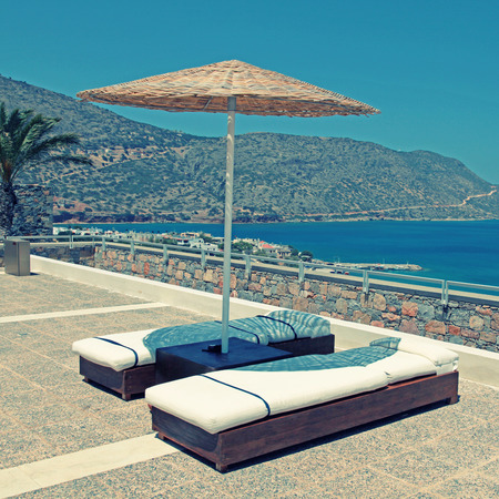 Sun beds and umbrellas on terrace in a luxury summer resort with Mediterranean sea view (Crete, Greece).  photo
