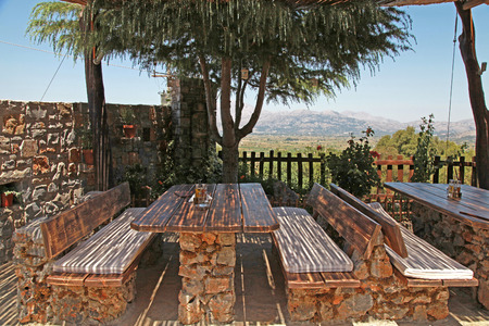 Wooden tables and benches in rural outdoor cafe, Crete, Greece photo