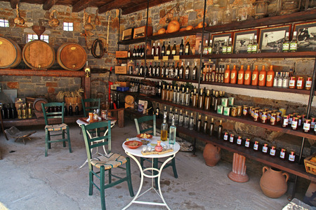 LASSITHI, GREECE - JULY 17, 2012: Interior with wine barrels and bottles in the old cellar of a winery, Lassithi, Crete, Greece.