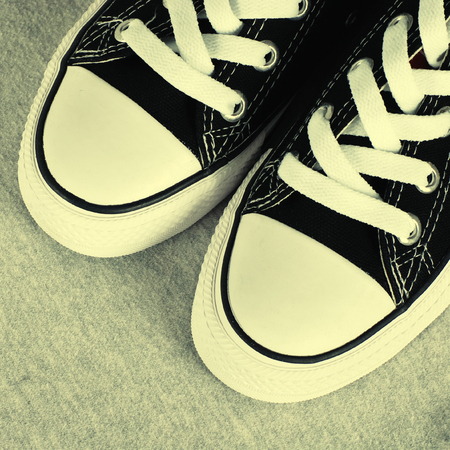 A pair of black canvas sneakers on grey textile background ,  square image photo