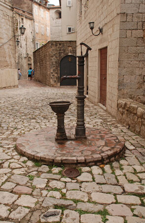 Vintage water well in a medieval town in Kotor, Montenegro photo