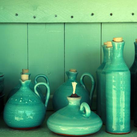 turquoise glazed ceramic pitchers in green shelf , Crete , Greece   photo
