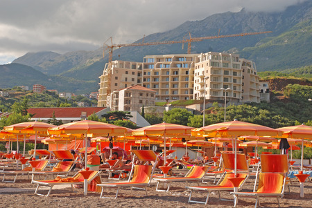 BUDVA, MONTENEGRO - JULY 25, 2011: Orange umbrellas and sun chairs on Mediterranean beach and construction of modern seaview apartments on green scenic hills, Budva, Montenegro