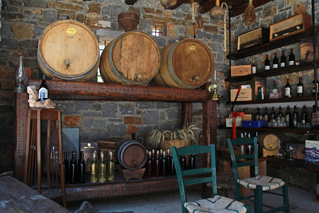 wine industry: LASSITHI, GREECE - JULY 17, 2012: Interior with wine barrels and bottles in the old cellar of a winery, Lassithi, Crete, Greece.