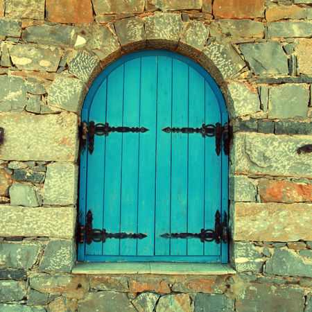 Vintage window with blue close shutters in old stone wall, Crete, Greece.    photo