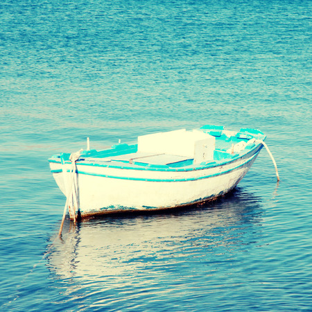 Blue and white old wood boat at a Mediterranean sea(Greece). photo