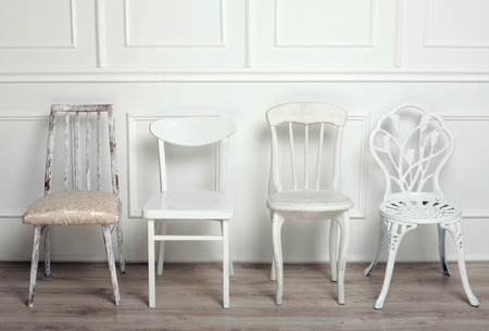 the stool: Set of white wooden vintage chairs standing in front of a white wooden wall on light parquet floor.