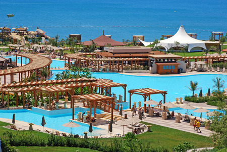 ANTALYA, TURKEY - JULY 15, 2007:  Swimming pools recreation area and Mediterranean Sea view on summer luxury resort, Antalya, Turkey