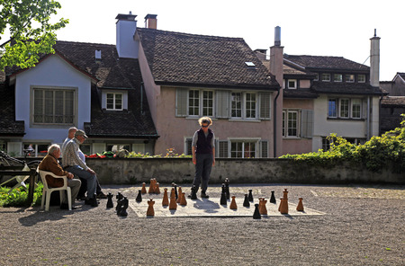 play the old park: ZURICH, SWITZERLAND - MAY 05, 2013: Old buildings and local men play traditional oversized street chess in the Lindenhof Park , center of Zurich, Switzerland. Editorial