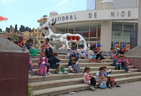 french ethnicity: NICE, FRANCE - MAY 14, 2013: Children on steps of the Museum of Contemporary Art, major cultural and touristic landmark in Nice, France