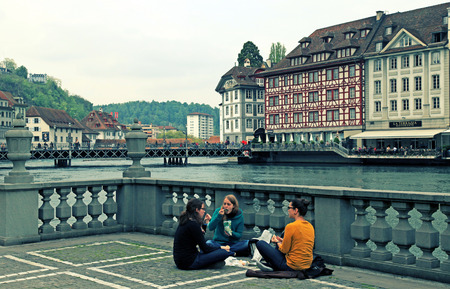 LUCERNE, SWITZERLAND - MAY 06, 2013: Cityscape with Lucerne city view, foot bridge and young women on the banks of Reuss River in Lucerne, Switzerland.