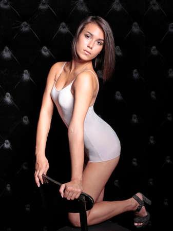brunett: Beautiful sensual woman with chair on black velvet background
