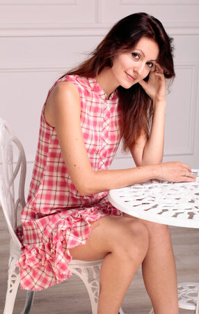 Young beautiful brunette woman in summer dress sitting near a table in white studio interior photo