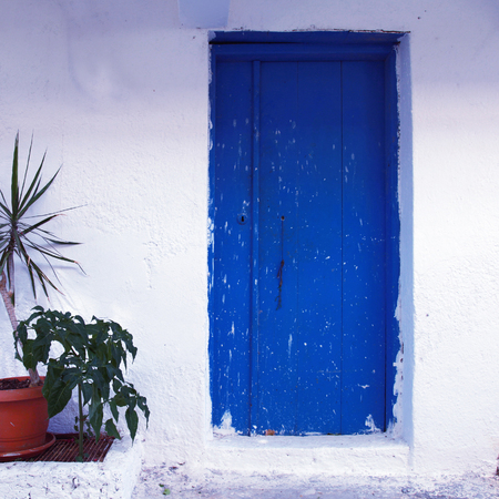 blue wood painted door at old traditional house (Crete, Greece), square toned image, instagram effect