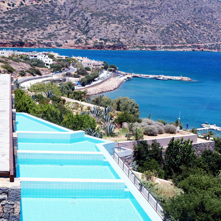 Summer sea resort with balkony and row of private swimming pools(Greece). square toned image, instagram effect